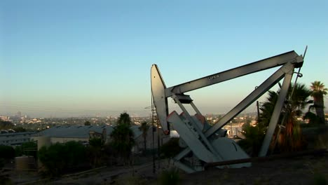 An-oil-well-pumps-at-dawn-with-a-sprawling-suburban-landscape-behind