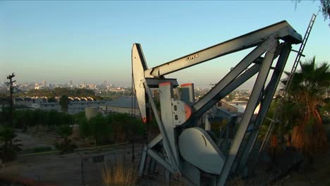 An-oil-well-pumps-oil-with-a-sprawling-suburban-landscape-behind