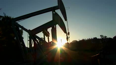 A-pump-jack-is-silhouetted-against-the-sun