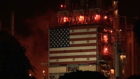 An-American-flag-mural-decorates-the-side-of-an-oil-refinery-at-night