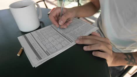 A-person-works-on-a-newspaper-puzzle-while-smoking-and-drink-coffee