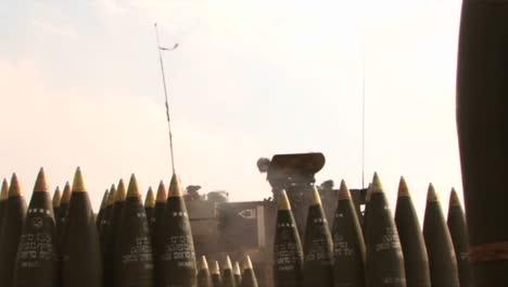 An-army-solider-in-Iraq-stands-amongst-shells-as-a-tank-gun-fires-