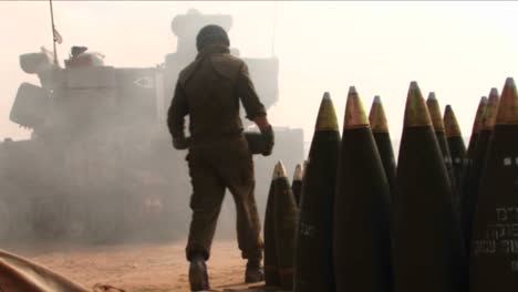 Israeli-soldier-stands-by-as-a-tank-fires-shells-into-Lebanon-then-loads-more-shells