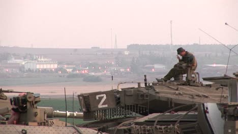 An-Israeli-army-soldier-sits-atop-a-tank-at-the-Gaza-Strip-border