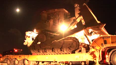 An-Israeli-armored-bulldozer-is-unloaded-from-a-flatbed-truck-for-night-patrol-along-the-Gaza-Strip
