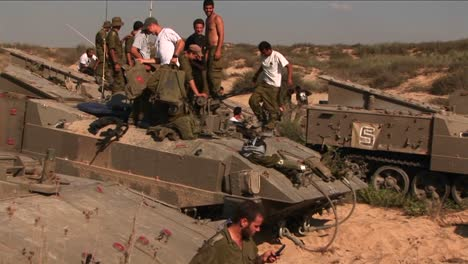 Israeli-soldiers-stand-on-top-of-their-armored-personnel-carriers-during-a-break-in-battle
