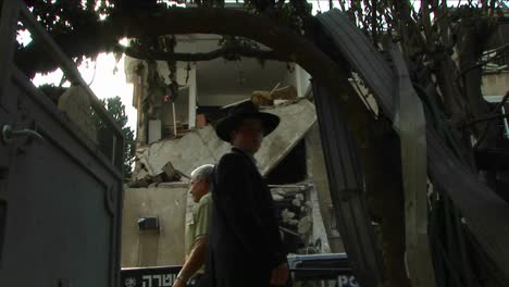 Pedestrians-in-Haifa-pass-by-an-apartment-building-destroyed-by-a-rocket-attack