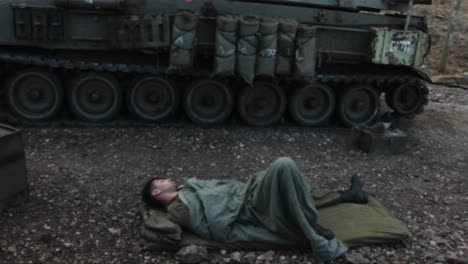 An-Israeli-army-soldier-sleeps-on-the-ground-next-to-his-tank-during-the-Israel-Lebanon-war