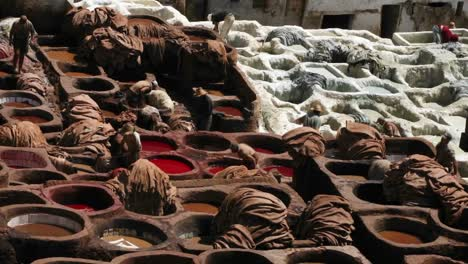 A-time-lapse-of-people-dying-clothes-in-large-clay-vats-
