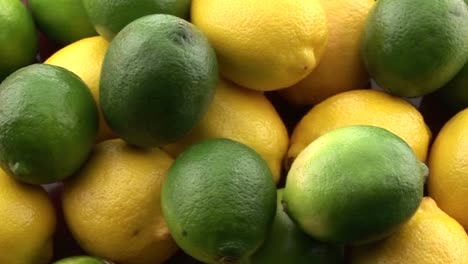 Slow-zoom-into-yellow-lemons-sit-in-a-pile-with-green-limes