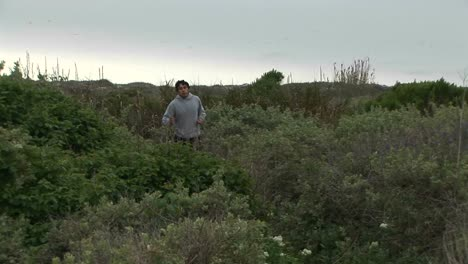 A-young-man-jogs-by-on-a-lush-trail