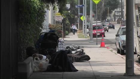 Obdachlose-Sitzen-Auf-Einem-Bürgersteig