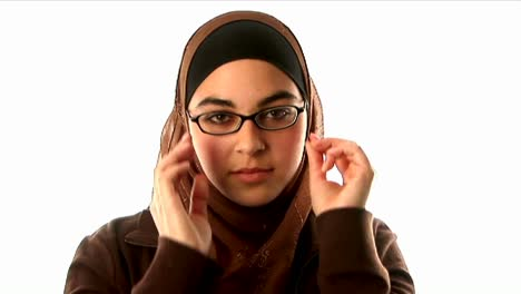 A-woman-wearing-an-underscarf-headscarf-and-sweater-puts-on-her-glasses