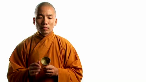 A-Buddhist-monk-wearing-an-orange-robe-taps-a-bell-with-a-small-stick