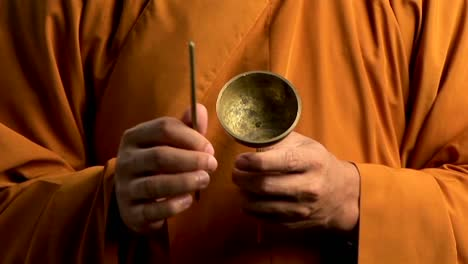 A-Buddhist-monk-wearing-an-orange-robe-taps-a-bell-with-a-small-stick-1