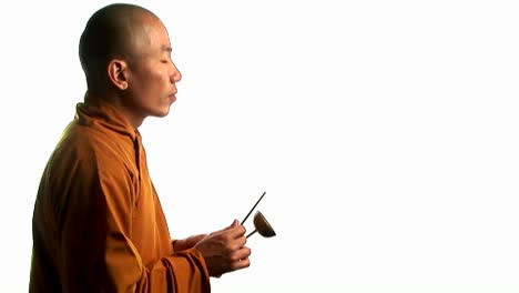 A-Buddhist-monk-wearing-an-orange-robe-taps-a-bell-with-a-small-stick-2