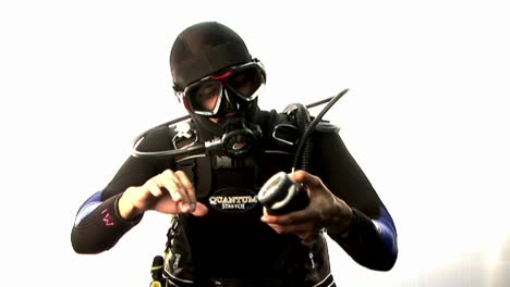 A-scuba-diver-pretends-to-swim-and-check-his-depth-on-land-