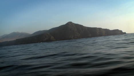 A-boat-passes-through-the-water-with-other-boats-and-mountains-in-the-distance