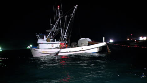 A-fishing-boat-equipped-with-a-net-and-a-winch-is-working-at-night