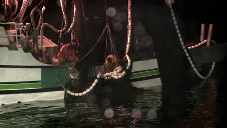 A-crew-member-reaches-into-a-fishing-vessels-net