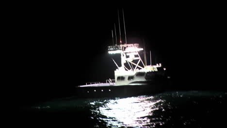A-boat-sits-in-the-water-at-night-while-a-man-works-on-the-deck