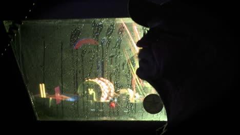 A-man-looks-through-a-boat-window-as-the-rain-falls
