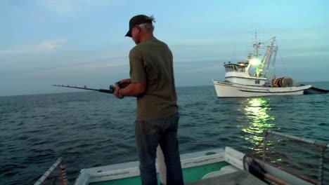 Un-Hombre-Pesca-Desde-La-Parte-Trasera-De-Un-Bote-Pequeño