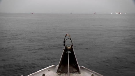 A-boat-passes-through-the-water-with-a-swimmer-and-other-boats-in-the-distance