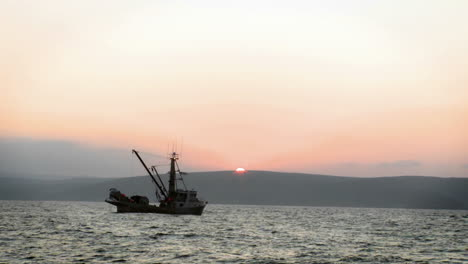Two-boats-are-sitting-in-the-water-as-the-sun-sets-over-the-mountains