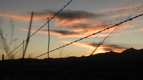 The-sun-sets-over-an-area-protected-by-barbed-wire