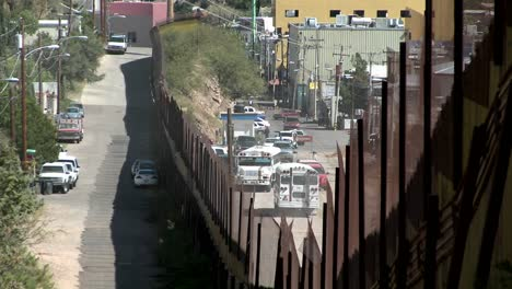 A-border-fence-shows-the-separation-of-a-community-between-a-rural-area-and-a-densely-populated-area