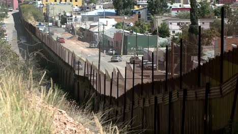 A-hillside-view-front-behind-a-large-fence-looking-down-on-an-intercity-street-neighborhood