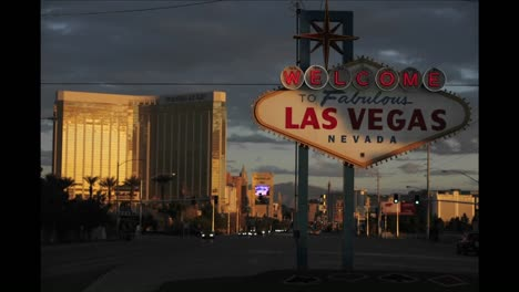 A-sign-welcomes-people-to-Las-Vegas-as-traffic-and-pedestrians-pass-by