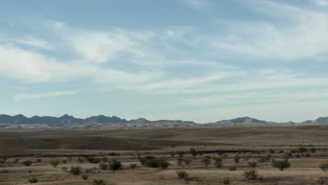 Clouds-pass-over-a-remote-area-and-cars-go-by-on-a-road-in-a-time-lapse-sequence