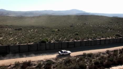 A-car-drives-down-a-road-bordered-by-a-fence