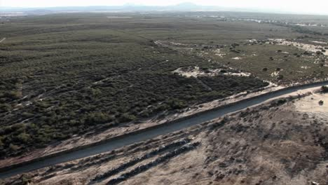 A-daytime-aerial-view-of-a-waterway-traversing-through-a-minimally-developed-landscape
