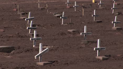 Many-white-wooden-crosses-marked-only-with-the-phrase-no-olvidado-are-displayed-in-a-dirty-field