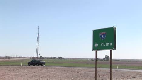 A-truck-drives-by-a-road-sign-pointing-to-Yuma