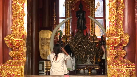 A-young-woman-enters-a-Buddhist-temple-in-Thailand-and-sits-to-and-begins-to-pray
