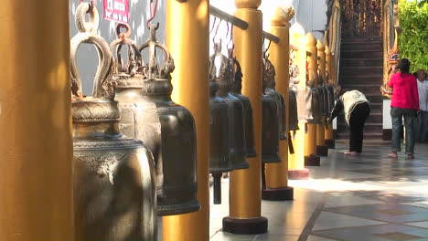 People-look-at-gold-urns-for-sale-in-a-marketplace
