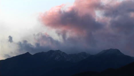 Dark-clouds-roll-in-over-low-mountains-near-sunset