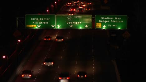 A-time-lapse-of-vehicles-driving-on-the-freeway-and-under-signs-at-night