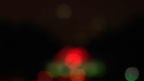A-rack-focus-of-vehicles-driving-on-the-freeway-and-into-the-city-at-night