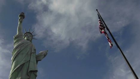 A-time-lapse-of-clouds-moving-over-the-Statue-of-Liberty-and-an-American-flag