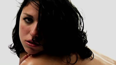 A-topless-woman-with-damp-hair-looks-in-the-direction-of-the-camera