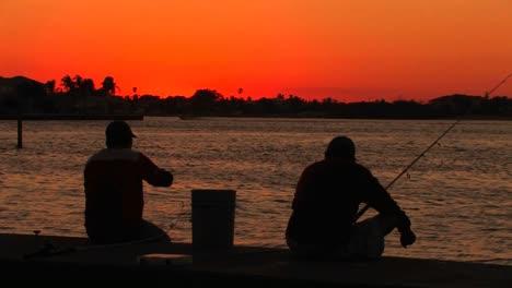 Silueta-De-Dos-Hombres-Pescando-Al-Atardecer