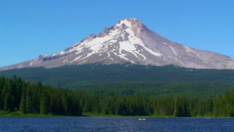 A-canoe-crosses-a-lake-surrounded-by-pine-trees-and-a-snowcapped-mountain-at-Trillium-Lake-Mt-Hood-in-Oregon