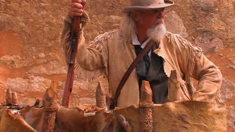 Un-Anciano-Sostiene-Un-Rifle-Y-Viste-Una-Chaqueta-De-Cuero-Pionera