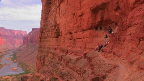 A-beautiful-shot-of-tourists-on-a-trail-along-the-Grand-Canyon-at-magic-hour