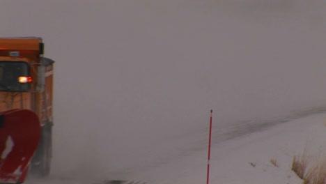 A-snowplow-works-on-a-road-in-heavy-winter-snow